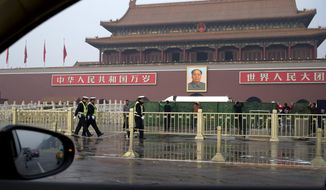 Traffic policemen walk past plainclothes policemen place green net shields in front of Tiananmen Gate following a car fire in Beijing Monday, Oct. 28, 2013. A sport-utility vehicle veered into a crowd in front of Beijing's Forbidden City and then crashed and caught fire Monday, killing three people and injuring several, police said. (AP Photo/Andy Wong)