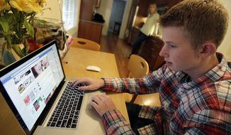 In this Oct. 24, 2013 photo, Mark Risinger, 16, checks his Facebook page on his computer as his mother, Amy Risinger, looks on at their home in Glenview, Ill. The recommendations are bound to prompt eye-rolling and LOLs from many teens but an influential pediatrician's group says unrestricted media use has been linked with violence, cyber-bullying, school woes, obesity, lack of sleep and a host of other problems. Mark's mom said she agrees with restricting kids' time on social media but that deciding on other media limits should be up to parents. (AP Photo/Nam Y. Huh) **FILE**