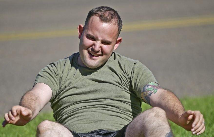 """In a Wednesday, Oct. 16, 2013 photo,  overweight service member who failed the so-called """"tape test"""" struggles doing sit ups during a workout where he hopes to improve his conditioning and avoid being dismissed from the military, at the Marine Corps Recruit Depot in San Diego. Doctors say a number of military personnel are turning to liposuction to remove excess fat from around the waist so they can pass the Pentagon's body fat test. Some service members say they have no other choice because the Defense Department's method of estimating body fat is weeding out not just flabby physiques but bulkier, muscular builds. A number of fitness experts and doctors agree, and they're calling for the military's fitness standards to be revamped.  (AP Photo/Lenny Ignelzi)"""