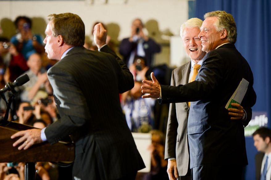 Sen. Mark Warner (D-Va.), left, introduces President Bill Clinton and Virginia gubernatorial candidate for Governor Terry McAuliffe, right, at Herndon Middle School, Herdon, Va., Monday, October 28, 2013. (Andrew Harnik/The Washington Times)