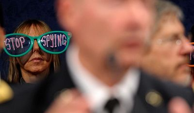 Protesters, including Code Pink co-founder Medea Benjamin (left), listen as NSA Director Gen. Keith B. Alexander testifies Tuesday on potential changes to the intelligence act that is the heart of revelations about U.S. spying at home and abroad. (Associated Press)