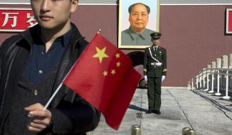 ** FILE ** A tourist holds up a Chinese flag as he poses for photos near a Chinese paramilitary policeman on duty in front of former Chinese leader Mao Zedong's portrait on Tiananmen Gate, close to the site of an incident Monday where a car plowed through a crowd before it crashed and burned in Beijing, China, Tuesday, Oct. 29, 2013. (AP Photo/Ng Han Guan)