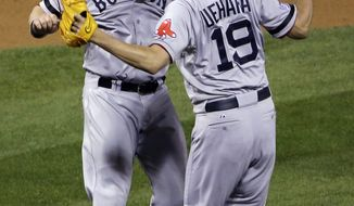 Boston Red Sox relief pitcher Koji Uehara celebrates with teammate Dustin Pedroia after getting St. Louis Cardinals' Matt Holliday to fly out and end Game 5 of baseball's World Series Monday, Oct. 28, 2013, in St. Louis. The Red Sox won 3-1 to take a 3-2 lead in the series. (AP Photo/David J. Phillip)