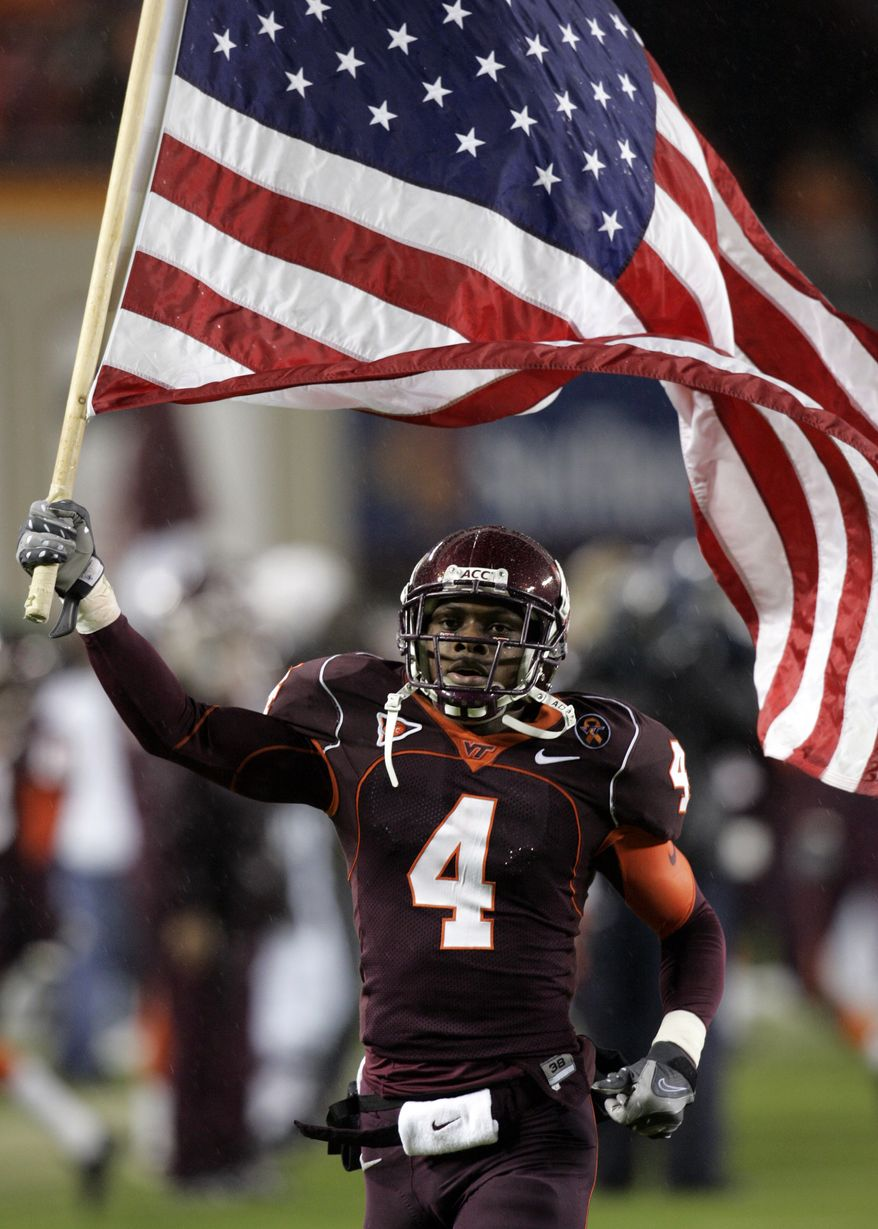 Virginia Tech flanker Eddie Royal (4) carries the US flag into the stadium prior to the Boston College-Virginia Tech  college football game at Lane Stadium in Blacksburg, Va., Thursday, Oct. 25, 2007. BC won the game 14-10.  (AP Photo/Steve Helber)