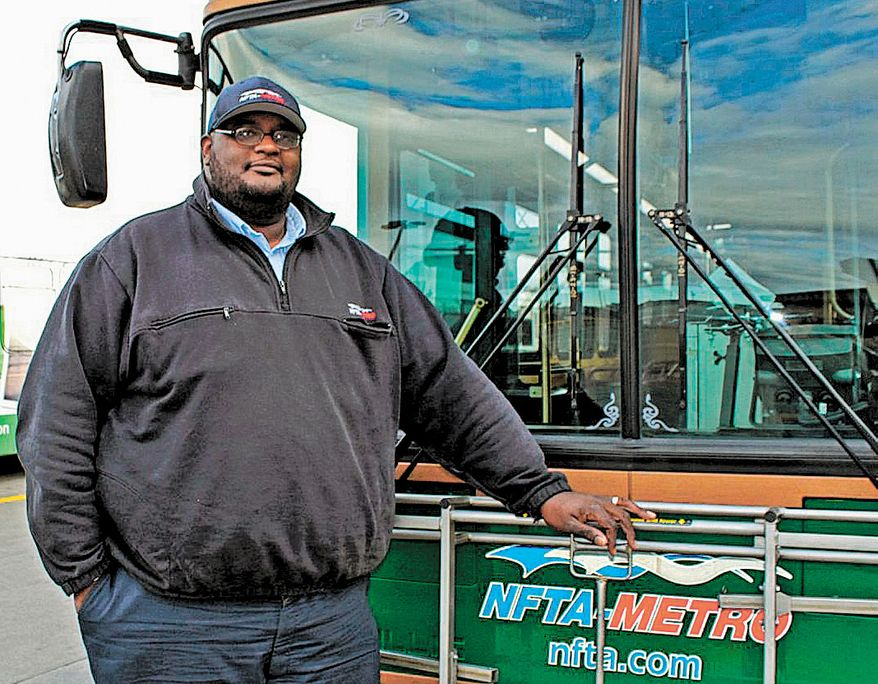 Darnell Barton, a driver for the Niagara Frontier Transportation Authority, poses in front of a bus in Buffalo, N.Y., on Monday, Oct. 28, 2013. On Oct. 18, Mr. Barton's decisive action stopped a woman from leaping from a roadway bridge to her death on a highway below. Caught between the rules of his job and his training as a first responder, Mr. Barton stopped his bus, grabbed the woman and brought her back over the rail to safety. (AP Photo/Niagara Frontier Transportation Authority, Doug Hartmayer)
