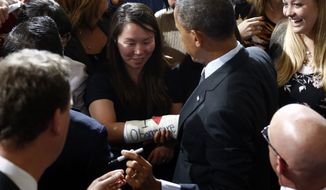 "President Barack Obama gets ready to sign the ""I Love Obamacare"" cast of Cathey Park of Cambridge, Mass., after he spoke at Boston's historic Faneuil Hall about the federal health care law, Wednesday, Oct. 30, 2013. Faneuil Hall is where former Massachusetts Republican Gov. Mitt Romney, Obama's rival in the 2012 presidential election, signed the state's landmark health care law in 2006, with top Democrats standing by his side. (AP Photo/Charles Dharapak)"