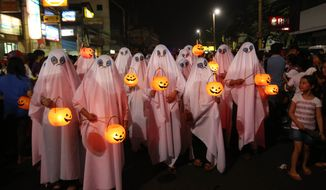 Filipinos wear ghost costumes as they join a Halloween Parade in Marikina city, east of Manila, Philippines on Wednesday, Oct. 30, 2013. Hundreds of residents and government employees joined the parade as the country prepares to observe All Saints Day on Nov. 1. (AP Photo/Aaron Favila)