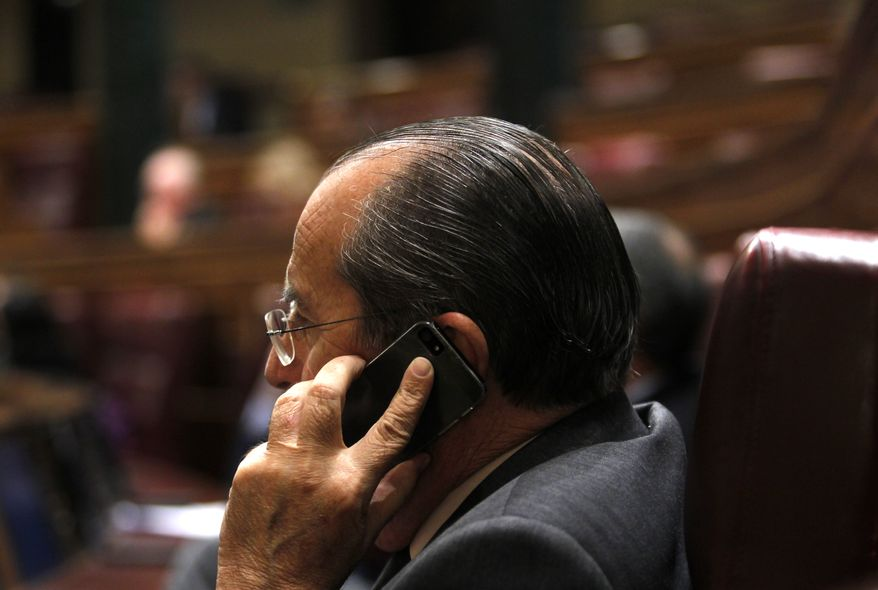 """A Spanish lawmaker talks on his cell phone at the Spain's parliament, in Madrid, Wednesday, Oct. 30, 2013. Speaking in parliament, Spain's Prime Minister Mariano Rajoy said Spain was taking the surveillance allegations seriously and that the head of Spain's intelligence services will address Parliament over allegations that Spain was a target for surveillance by the U.S. National Security Agency. He reiterated that if confirmed, such activity is """"inappropriate and unacceptable between partners and friends."""" Up to now the Spanish government insists it is unaware of any U.S. spying. (AP Photo/Francisco Seco)"""