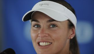 FILE - In this  picture taken July 9, 2013 Washington Kastles' Martina Hingis, of Switzerland, attends a press conference prior a World Team Tennis match against the Boston Lobsters, in Washington. Martina Hingis has been questioned by Swiss police after her estranged husband said he was attacked by the five-time Grand Slam champion and her family. Schwyz canton police spokesman Florian Grossmann says Hingis,her mother Melanie Molitor and her mother's boyfriend Mario Widmer were interviewed at its headquarters last week. Grossmann tells The Associated Press the canton justice department will decide possible further action. No timetable was set for a decision. French equestrian athlete Thibault Hutin has said he was attacked on Sept. 23 at his home in Feusisberg. Hutin claimed Hingis and Molitor hit him, and Widmer struck him with a DVD player.   (AP Photo/Nick Wass, File)