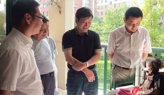 In a photo originally posted to a county government website, local officials purportedly visit a 100-year-old woman in Anhui province.  Credit Ningguo Civil Affairs Department via Chinanews.com