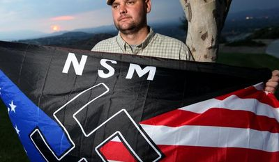 ** FILE ** Jeff Hall holds a neo-Nazi flag while standing at Sycamore Highlands Park near his home in Riverside, Calif., in October 2010. (AP Photo/Sandy Huffaker)