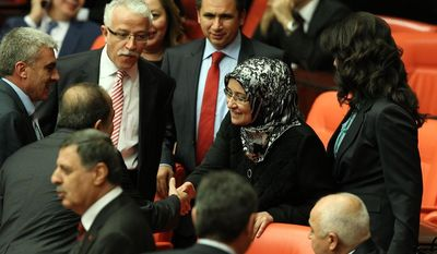 Gulay Samanci, surrounded by other lawmakers, is one of four female members of the ruling Justice and Development Party to wear headscarves to a session of the Grand National Assembly in Ankara, Turkey, on Thursday, Oct. 31, 2013, to mark the end of a longstanding ban in the chamber. (AP Photo)