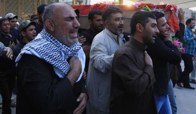 Members of an Iraqi Shiite fighters militant group called Kataib Sayyid al-Shuhadaa chant slogans against the Sunni-dominated Free Syrian Army rebel group and the al-Qaida-affiliated Jabhat al-Nusra as they carry the coffin of a Shiite fighter during a funeral procession in the Shiite holy city of Najaf, 100 miles (160 kilometers) south of Baghdad, Iraq, Tuesday, Oct. 29, 2013. (AP Photo)