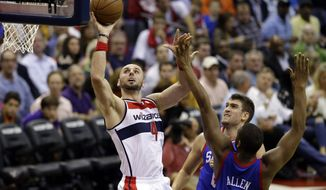 Washington Wizards center Marcin Gortat (4), from Poland, shoots against Philadelphia 76ers' Spencer Hawes (00) and Lavoy Allen (50) in the second half of an NBA basketball game, Friday, Nov. 1, 2013, in Washington. The 76ers won 109-102. (AP Photo/Alex Brandon)
