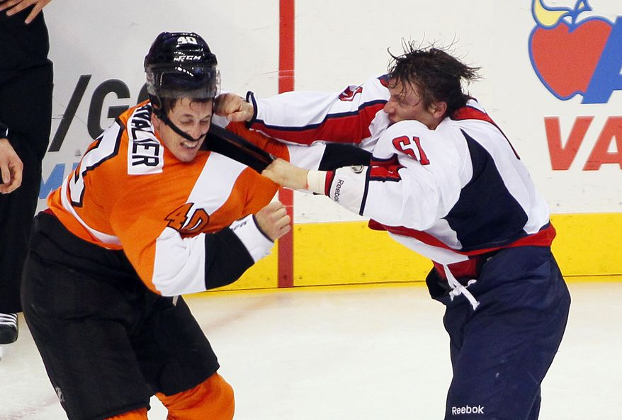 Philadelphia Flyers' Vincent Lecavalier, left, takes a punch to his head from  Washington Capitals' Steve Olesky knocking his helmet off during a melee in the third period of an NHL hockey game Friday, Nov. 1, 2013, in Philadelphia. The Capital won 7-0. (AP Photo/Tom Mihalek)