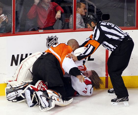 Linesman Francois St. Laurent, right, tries to pull Philadelphia Flyers goalie Ray Emery, top, off of Washington Capitals goalie Braden Holtby during a melee in the third period of an NHL hockey game Friday, Nov. 1, 2013, in Philadelphia. The Capital won 7-0. (AP Photo/Tom Mihalek)