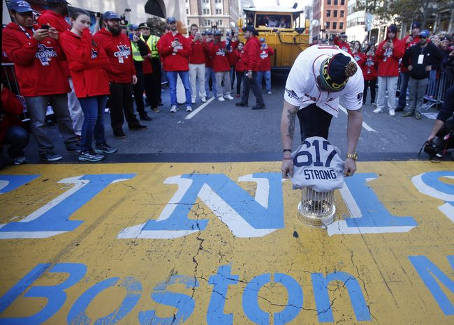 Boston Red Sox's Jonny Gomes places the championship trophy and a Red Sox baseball jersey at the Boston Marathon Finish Line during a pause in their World Series victory rolling rally in Boston, Saturday, Nov. 2, 2013, to remember those affected by the Marathon bombing. (AP Photo/Elise Amendola)