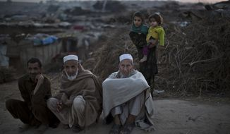 ** FILE ** Pakistani men, who were displaced with their families from Pakistan's tribal areas due to fighting between the Taliban and the army, sit on a roadside on the outskirts of Islamabad, Pakistan, Saturday, Nov. 2, 2013. The Pakistani Taliban confirmed the death of their leader, Hakimullah Mehsud, in a U.S. drone strike Saturday, a day after he was killed, as the group's leadership council met to begin the process of choosing a successor. (AP Photo/Muhammed Muheisen)
