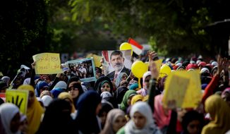 "Supporters of ousted Egyptian President Mohammed Morsi march in protest in Cairo on Sunday, Nov. 3, 2013, a day before the former leader's trial is set to begin. The Arabic on the poster at left reads, ""Bring back the soldiers to the front lines."" (AP Photo/Eman Helal)"