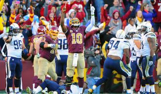 Washington Redskins quarterback Robert Griffin III (10) points to the heavens after defeating the San Diego Chargers 30-24 in overtime at FedExField, Landover, Md., November 3, 2013. (Preston Keres/Special for The Washington Times)