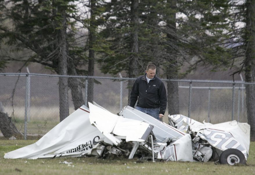 An FAA investigator Sunday, Nov. 3, 2013 examines the wreckage of a plane that crashed in Superior, Wis., Saturday after a midair collision with another plane. Both planes were carrying skydivers. No one was seriously injured in the incident. (AP Photo/The News-Tribune, Steve Kuchera)