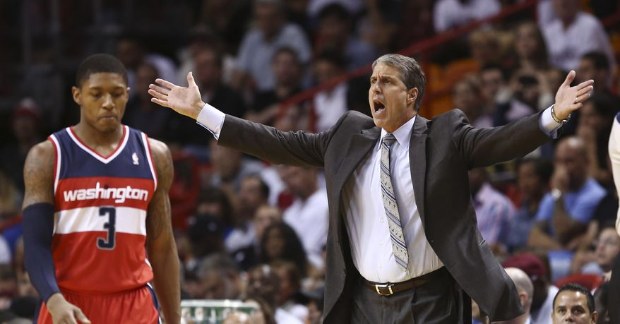 Washington Wizards coach Randy Wittman protests a penalty call against the team, after they fouled a Miami Heat player during the first half of an NBA basketball game in Miami, Sunday, Nov. 3, 2013. Bradley Beal walks past.  (AP Photo/J Pat Carter)