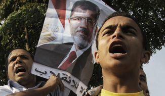 "Supporters of Egypt's ousted President Mohammed Morsi raise his poster with Arabic that reads, ""no to the coup,"" during a protest in front of the supreme constitutional court in Cairo, Egypt, Monday, Nov. 4, 2013. (AP Photo/Amr Nabil)"