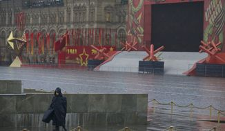 A security officer guards an empty decorated Red Square as Russian President Vladimir Putin places flowers at a nearby statue of Minin and Pozharsky, the leaders of a struggle against foreign invaders in 1612, to mark the National Unity Day in Moscow, Russia, Monday, Nov. 4, 2013. The national holiday of Unity Day was  established in 2005 to replace commemorations of the Bolshevik Revolution. The Red Square is decorated with stars for Nov.7, celebration, when Russia marks WWII 1941 military parade anniversary. (AP Photo/Alexander Zemlianichenko, pool)