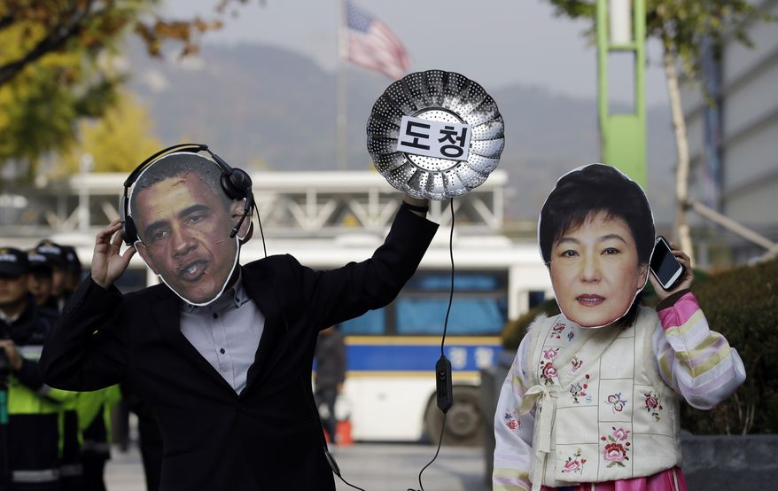 ** FILE ** South Korean protesters wearing masks of U.S. President Barack Obama, left, and South Korean President Park Geun-hye perform during a rally denouncing U.S. National Security Agency's alleged spying on its allies near the U.S. Embassy in Seoul, South Korea, Monday, Nov. 4, 2013. (AP Photo/Lee Jin-man)
