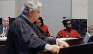 Jury selection for Dontae Morris, right, is underway in an Orlando, Fla. courtroom on Monday, Nov. 4, 2013, before Circuit Judge William Fuente. The judge in the foreground is asking prospective jurors questions about prior knowledge of this case. In back is Morris and members of his defense team. (AP Photo/Tampa Tribune, Jay Conner, Pool)