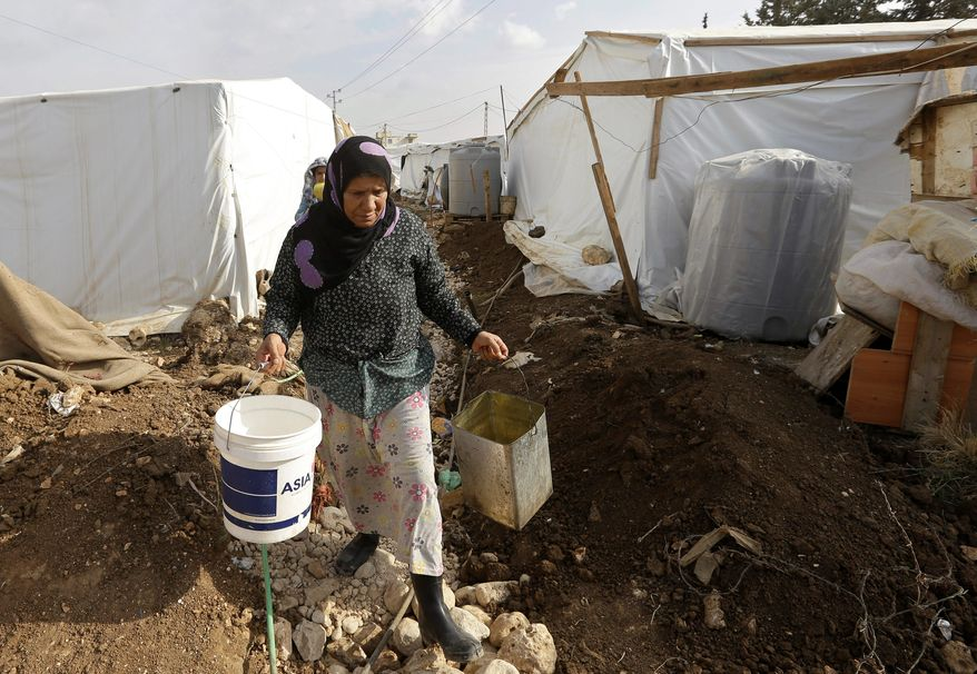 A Syrian woman carries buckets to fill with water at a refugee camp at Delhamiyeh village in the Bekaa valley in eastern Lebanon. More than 812,000 Syrians in Lebanon are urban refugees, who live not in camps but in cities and towns. (Associated Press)