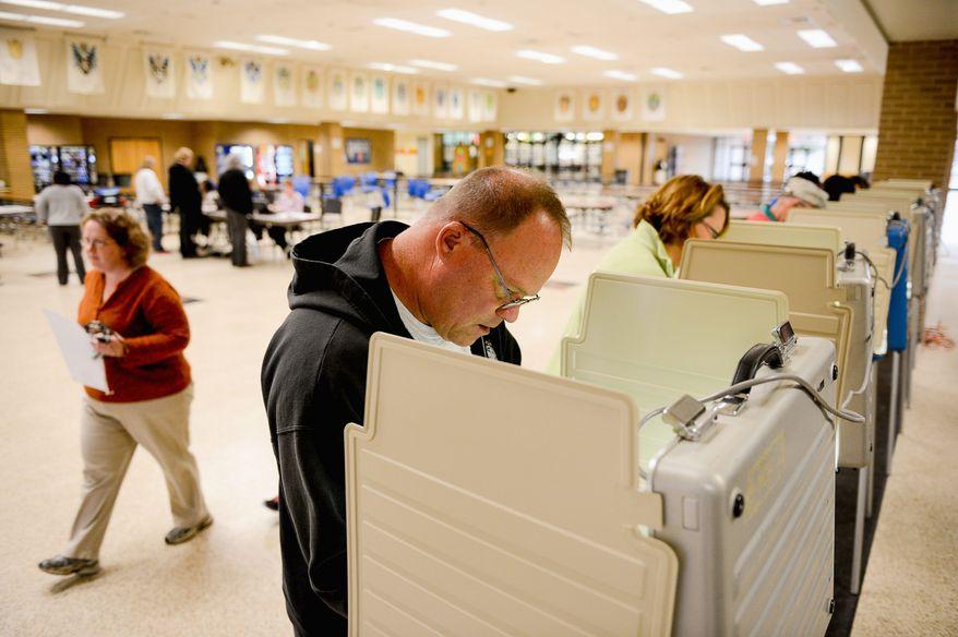 Rob Wilhoite [cq] of Mechanicsville, Va., center, votes for Virginia Governor at the Hanover Precinct at Atlee High School, Mechanicsville, Va., Tuesday, November 5, 2013. (Andrew Harnik/The Washington Times)