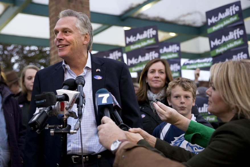 Virginia Democratic gubernatorial candidate Terry McAuliffe answers questions from the media after voting on election day in McLean, Va. on Tuesday, Nov. 5, 2013. At right of McAuliffe are his wife Dorothy and son Peter. (AP Photo/Jacquelyn Martin)