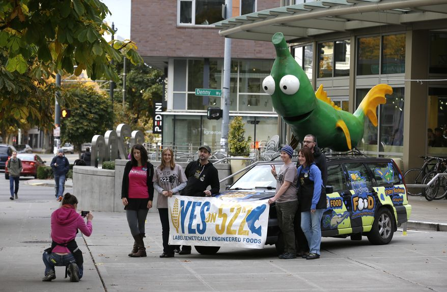 Supporters of Initiative 522 pose for a photo in front of a car with a figurine of a soybean crossed with a fish on it in front of a Whole Foods Market in downtown Seattle, on Election Day, Tuesday, Nov. 5, 2013. The vehicle was promoting a Yes vote on Initiative 522,  which would require the labeling of  food that contains genetically modified ingredients. I-522 supporters say consumers have the right to know what's in the food they buy, while opponents say the measure would lead to higher food costs. (AP Photo/Ted S. Warren)