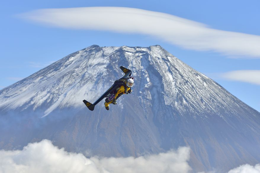 In this photo taken Friday, Nov. 1, 2013 and provided by Breitling, Yves Rossy, known as the Jetman, flies by Mount Fuji in Japan. The Swiss aviator jumped from a helicopter at an altitude of 3,600 meters (11,811 feet) and successfully flew the jet-powered carbon-Kevlar Jetwing around the 3,776-meter (12,388-foot)-tall mountain, Japan's highest peak, which was recognized as a UNESCO World Heritage site in June. (AP Photo/Katsuhiko Tokunaga, Breitling) EDITORIAL USE ONLY, NO SALES