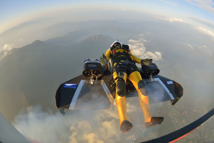 In this photo taken Friday, Nov. 1, 2013 and provided by Breitling, Yves Rossy, known as the Jetman, jumps from a helicopter near Mount Fuji in Japan. The Swiss aviator jumped from a helicopter at an altitude of 3,600 meters (11,811 feet) and successfully flew the jet-powered carbon-Kevlar Jetwing around the 3,776-meter (12,388-foot)-tall mountain, Japan's highest peak, which was recognized as a UNESCO World Heritage site in June. (AP Photo/Katsuhiko Tokunaga, Breitling) EDITORIAL USE ONLY, NO SALES