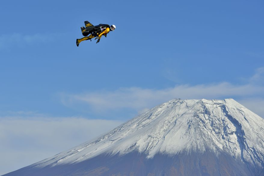 In this photo taken Wednesday, Oct. 30, 2013 and provided by Breitling, Yves Rossy, known as the Jetman, flies by Mount Fuji in Japan. The Swiss aviator jumped from a helicopter at an altitude of 3,600 meters (11,811 feet) and successfully flew the jet-powered carbon-Kevlar Jetwing around the 3,776-meter (12,388-foot)-tall mountain, Japan's highest peak, which was recognized as a UNESCO World Heritage site in June. (AP Photo/Katsuhiko Tokunaga, Breitling) EDITORIAL USE ONLY, NO SALES