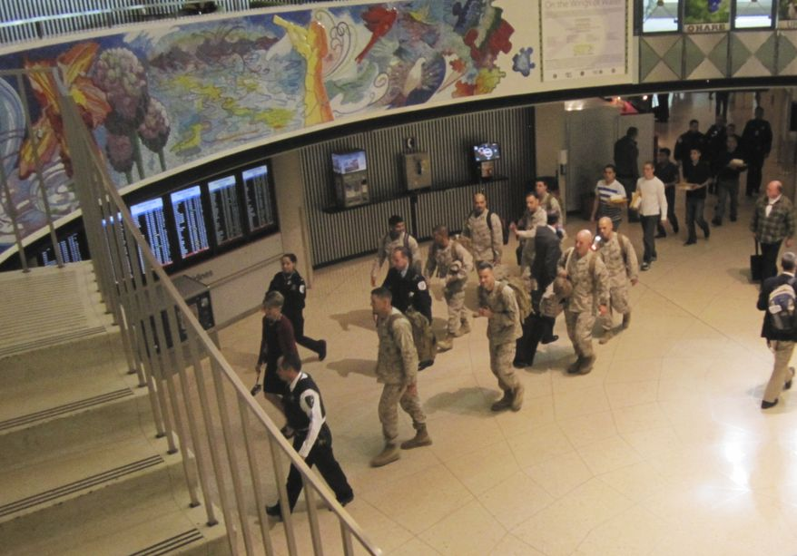"""This Monday, Nov. 4, 2013 photo provided by American Airlines shows a group of Marines walking through a terminal at Chicago's O'Hare International Airport  during part of their journey back home after a tour of duty in Afghanistan. The Marines were treated like heroes at the airport after a retired Marine and some others were not going to let them make the final leg of their journey to San Diego without thanking them for their service. After the plane they were on taxied underneath an arch of water from fire department hoses in what is called a """"water salute,' the 13 Marines walked into the terminal to the sight of a small crowd of cheering USO volunteers, firefighters, police officers and others who work at the airport. (AP Photo/Courtesy of American Airlines, Vic Ysais)"""