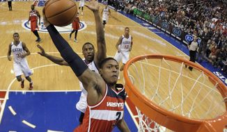 Washington Wizards' Bradley Beal (3) goes up for a dunk as Philadelphia 76ers' Thaddeus Young trails during the first half of an NBA basketball game, Wednesday, Nov. 6, 2013, in Philadelphia. (AP Photo/Matt Slocum)