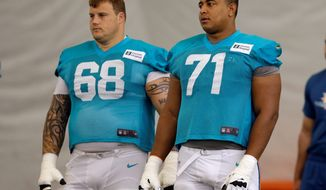The Miami Dolphins' Richie Incognito (68) sent text messages to teammate Jonathan Martin (71) that were racist and threatening, said people familiar with the situation. Incognito was suspended after Martin suddenly left the team. (Associated Press)