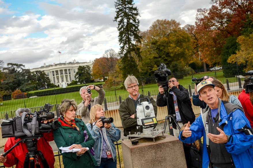 Chief Geodesist Dru Smith, right, and Kendall Fancher, center, with National Oceanic and Atmospheric Administration National Geodetic Survey give a demonstration for members of the media of the NOAA National Geodetic Survey as they continue to take measurements of monuments along and around the National Mall, Washington, D.C., Thursday, November 7, 2013. (Andrew Harnik/The Washington Times)