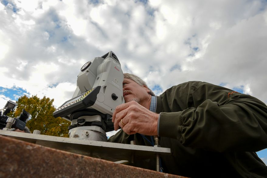 Kendall Fancher with the National Oceanic and Atmospheric Administration National Geodetic Survey gives a demonstration of the NOAA National Geodetic Survey as they continue to take measurements of monuments along and around the National Mall, Washington, D.C., Thursday, November 7, 2013. (Andrew Harnik/The Washington Times)