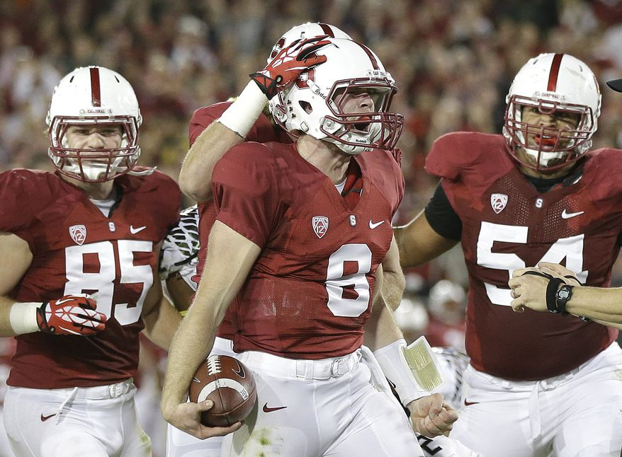 Stanford quarterback Kevin Hogan (8) celebrates with fullback Ryan Hewitt (85), tight end Charlie Hopkins (obscured) and guard David Yankey (54) after running for an 11-yard touchdown against Oregon during the second quarter of an NCAA college football game in Stanford, Calif., Thursday, Nov. 7, 2013. (AP Photo/Marcio Jose Sanchez)
