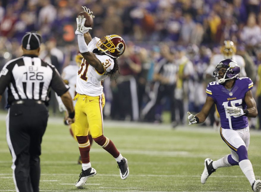 Washington Redskins strong safety Brandon Meriweather, left, intercepts a pass intended for Minnesota Vikings wide receiver Greg Jennings during the first half of an NFL football game, Thursday, Nov. 7, 2013, in Minneapolis. (AP Photo/Charlie Neibergall)
