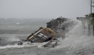 A house is engulfed by the storm surge brought about by powerful typhoon Haiyan that hit Legazpi city, Albay province Friday Nov.8, 2013 about 520 kilometers ( 325 miles) south of Manila, Philippines. Typhoon Haiyan, one of the most powerful typhoons ever recorded slammed into the Philippines on Friday, setting off landslides, knocking out power in one entire province and cutting communications in the country's central region of island provinces. (AP Photo/Nelson Salting)