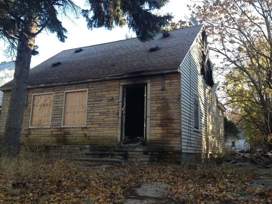"""This Thursday, Nov. 7, 2013 photo shows the fire damaged childhood home of rapper Eminem in Detroit.  Fire crews responded Thursday evening to the boarded-up bungalow, which is pictured on the cover of Eminem's just-released """"The Marshall Mathers LP 2."""" It also was on the musician's 2000 album """"The Marshall Mathers LP."""" The blaze damaged portions of the small home's top floor. The cause of the fire wasn't immediately known. (AP Photo/Detroit Free Press, Tammy Stables Battaglia)  DETROIT NEWS OUT;  NO SALES"""