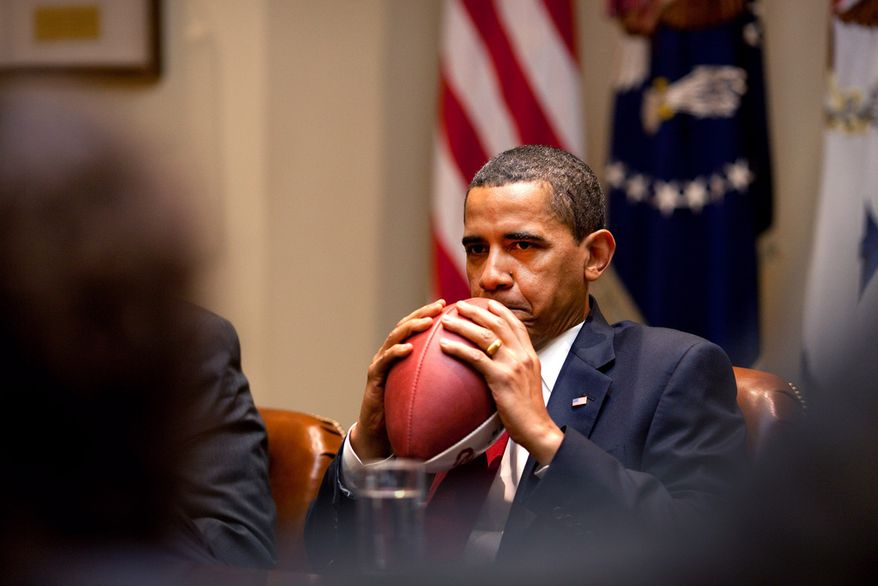 President Barack Obama holds a football while listening during a briefing with advisors in the Roosevelt Room of the White House May 4, 2009. (Official White House Photo by Pete Souza)