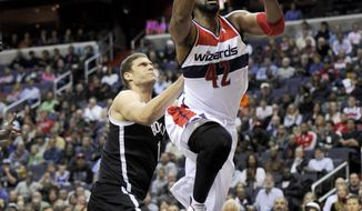 Washington Wizards power forward Nene (42), of Brazil, goes to the basket against Brooklyn Nets center Brook Lopez, left, during the second half of an NBA basketball game Friday, Nov. 8, 2013, in Washington. Lopez was called for a foul on the play. The Wizards won 112-108 in overtime. (AP Photo/Nick Wass)
