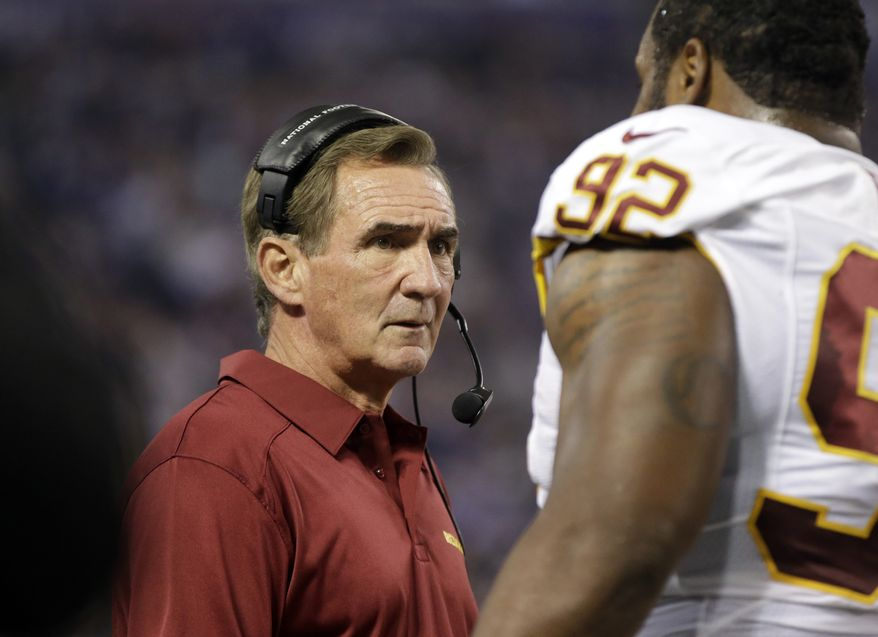 Washington Redskins head coach Mike Shanahan, left, talks with defensive lineman Chris Baker in an NFL football game against the Minnesota Vikings, Thursday, Nov. 7, 2013 in Minneapolis. (AP Photo/Jim Mone)