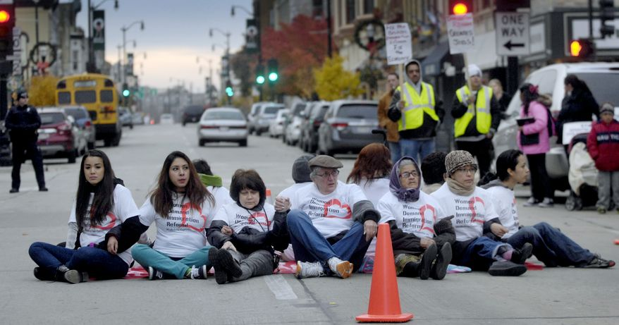 **FILE** Twelve women hold hands Friday, Nov. 8, 2013, as they block Sixth Street during an immigration reform protest outside Congressman Paul Ryan's office in Racine, Wis. (AP Photo/Journal Times, Gregory Shaver)